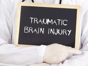 Doctor showing a sign that has traumatic brain injury written. TryMunity.